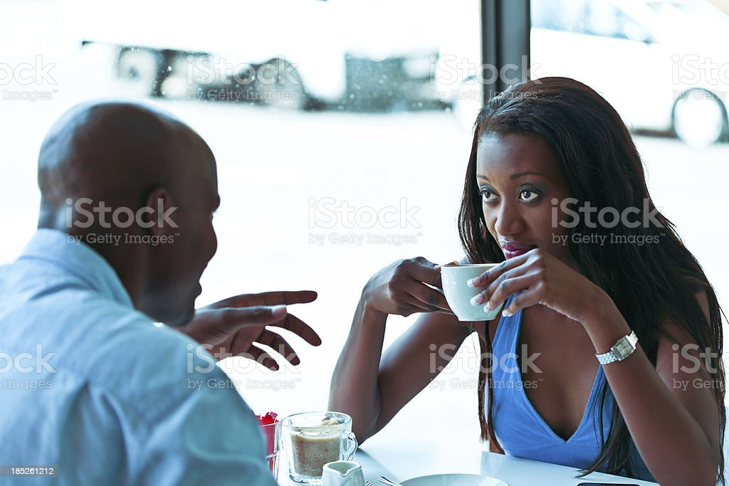 Date in cafe An attractive african couple enjoying coffee in the indoors restaurant. Adult Stock Photo