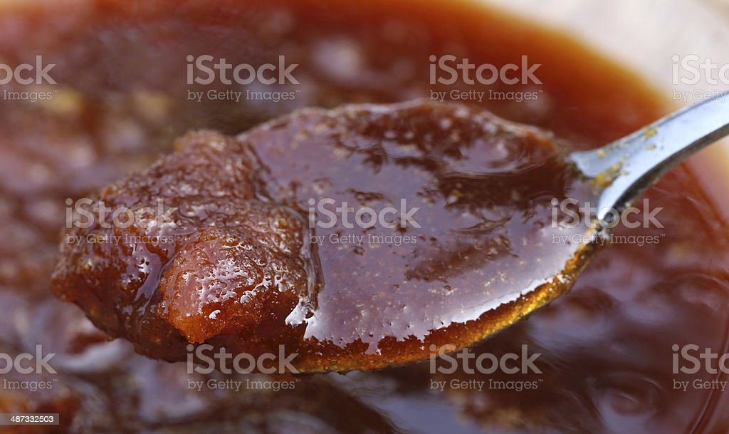 Date molasses with silver spoon stock photo