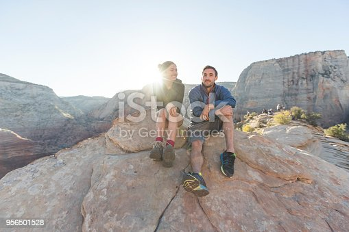 A young couple sit at the edge of a cliff, on a boulder at sunrise, and look around in wonder. They are surrounded by a majestic array of cliffs and rock formations. Their feet are dangling over the edge.