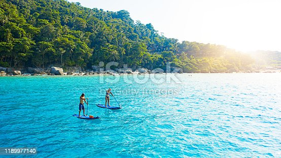 Shot of a man and woman paddle boarding across the sea