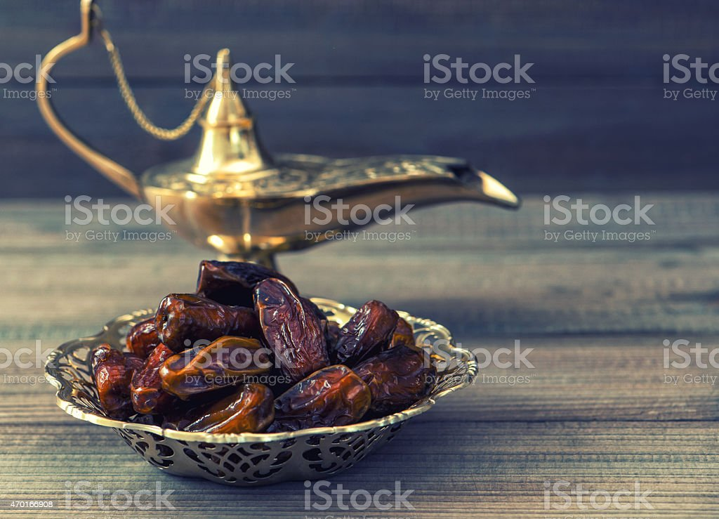 Dates and golden arabian lamp on wooden background. Oriental food stock photo