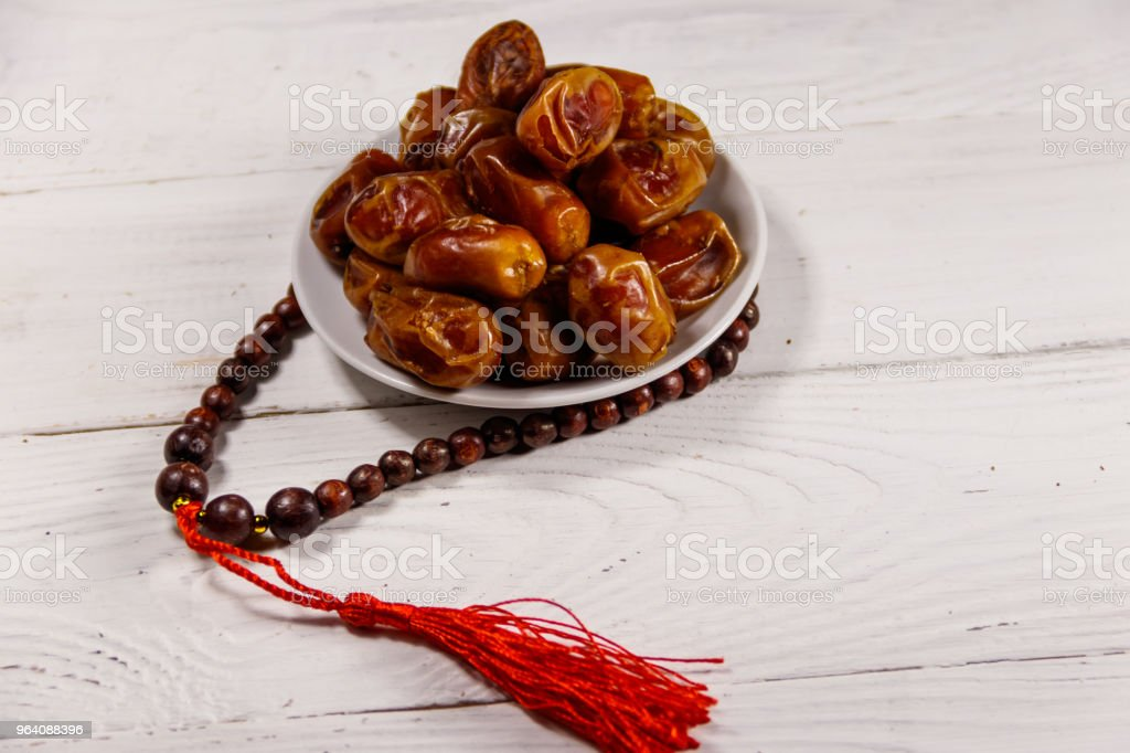 Dates fruit and rosary on white wooden table - Royalty-free Arab Culture Stock Photo