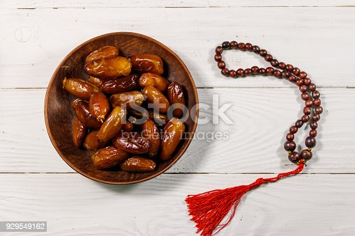 istock Dates fruit and rosary on white wooden table. Top view 929549162