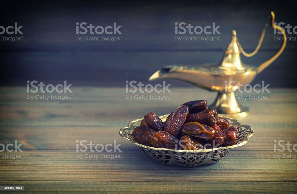 Dates in golden bowl and arabian Aladdin lamp. Vintage style stock photo