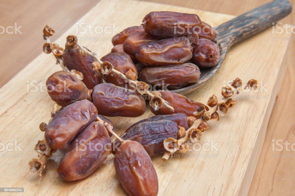 Dates de fruits dans une louche en bois sur fond en bois de palme - Photo