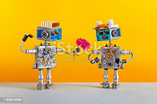 910163152 istock photo Dates robots. Romantic robot man gives a bouquet of pink roses flowers to a female robot. Dating agency or valentines wedding day card. Yellow background 1165929566