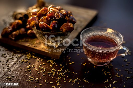 Dates tea in transparent glass cup along with some fennel seeds, cinnamon sticks and ginger well mixed and put together in tea.The horizontal well lit upshot of dates tea in a transparent glass cup.