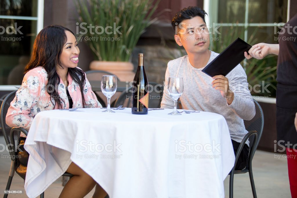 Dating Couple Paying Bill and Tip Gratuity at a Restaurant stock photo