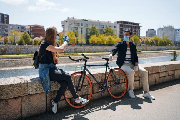 Dating-Paar im Gespräch mit zwei Metern Abstand im Freien an einem sonnigen Tag während einer Coronavirus-Pandemie – Foto