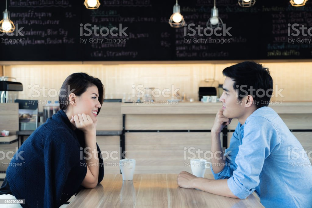 Dating in a cafe. Beautiful Asian lover couple sitting in a cafe enjoying in coffee and conversation. Love and romance. stock photo