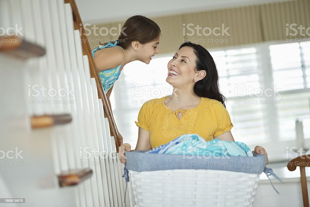 Daughter About To Kiss Mother With Laundry Basket stock photo