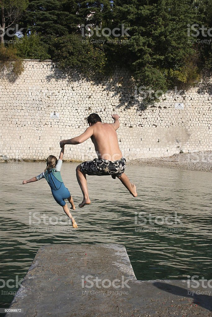 Daughter and daddy jumping royalty-free stock photo
