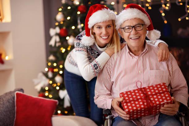 tochter und älteren vater im rollstuhl zusammen weihnachten feiern - geschenke eltern weihnachten stock-fotos und bilder