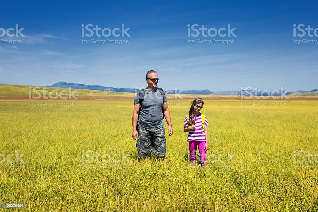 Daughter and father hiking in mountains. royalty-free stock photo