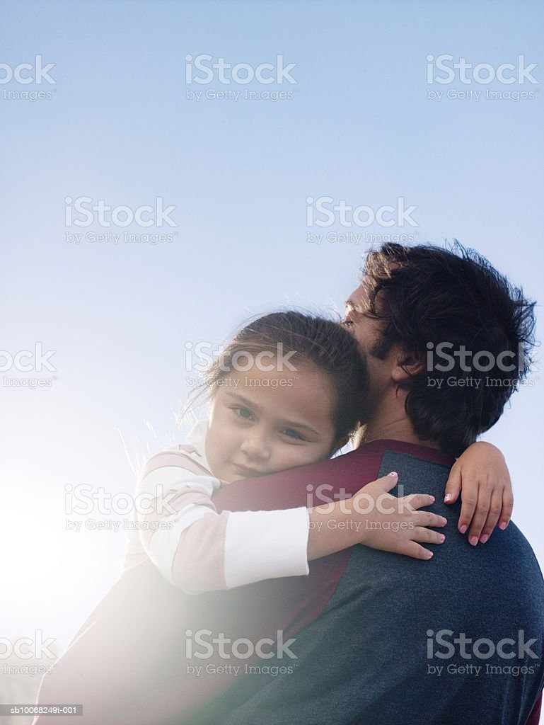 Daughter (6-7) and father hugging, girl looking at camera, outdoors royalty-free stock photo