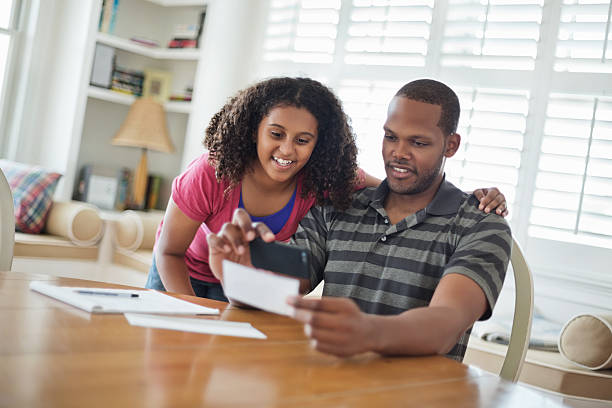 daughter and father paying bill using mobile phone - deposit slip stock photos and pictures