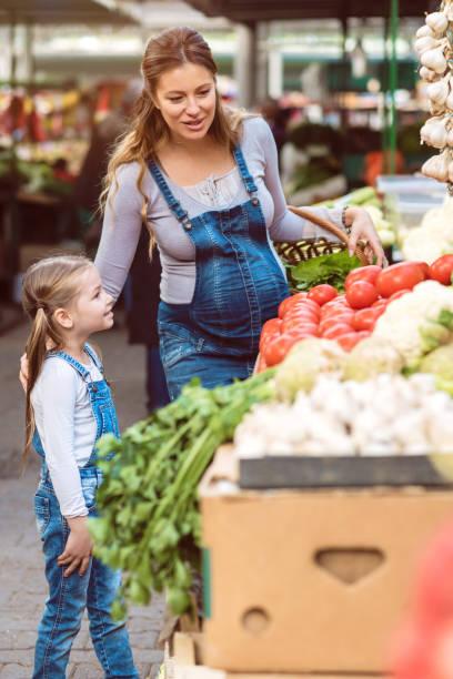 tochter und mutter auf dem lebensmittelmarkt - latzhose für schwangere stock-fotos und bilder