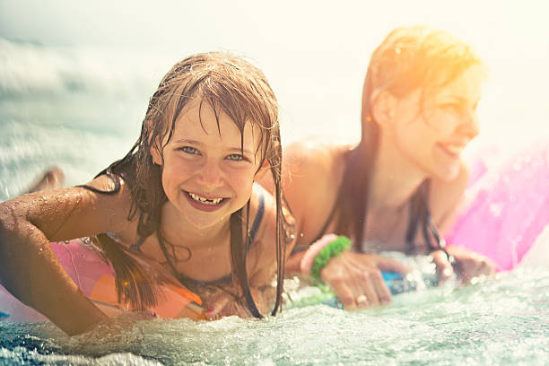 Daughter and mother having fun in sea Little girl and mother with inflateable raft being splashed by waves in sea. Candid smile and laugh of a cute little girl having fun with her mother. wading stock pictures, royalty-free photos & images
