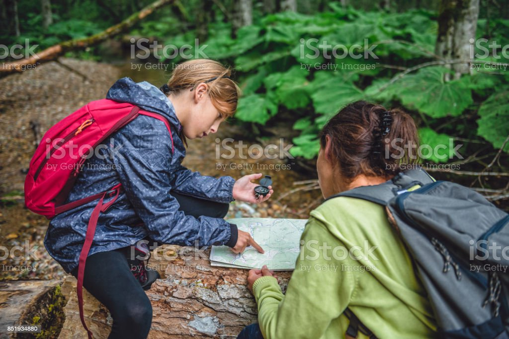 Daughter and mother hiking in forest and using compass stock photo