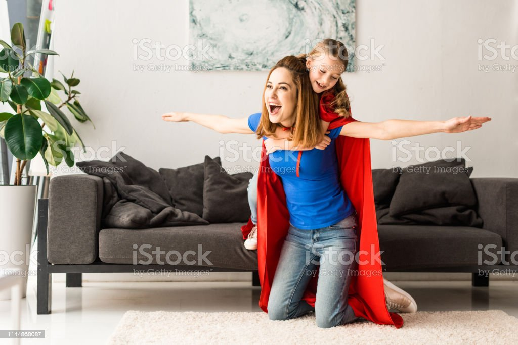 daughter and mother in red cloaks smiling and playing at home daughter and mother in red cloaks smiling and playing at home Adult Stock Photo