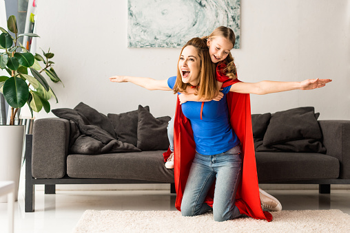 Daughter And Mother In Red Cloaks Smiling And Playing At Home Stock Photo - Download Image Now