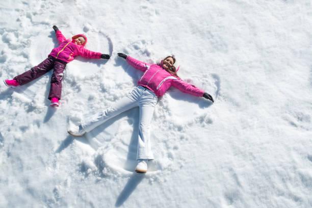 tochter und mutter verlegung auf schnee - schneespiele stock-fotos und bilder