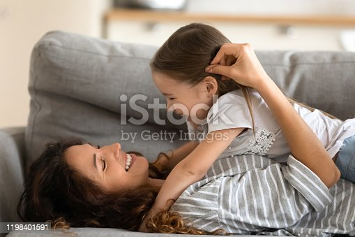 1070262182 istock photo Daughter and mother lying on couch enjoy moment of tenderness 1198401591