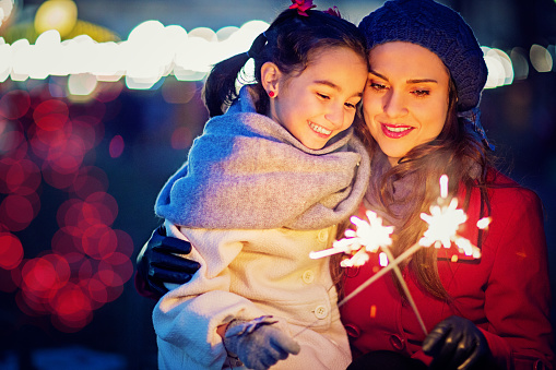 Mother is holding her beloved daughter and holding fireworks.