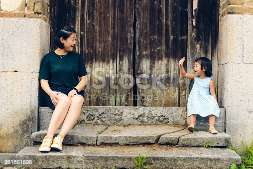 Chinese Daughter and mother sitting on the stairs in the front door.