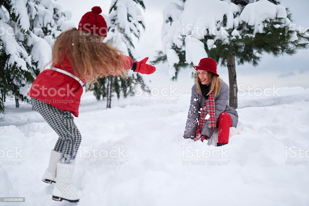daughter and mother playing with snow stock photo
