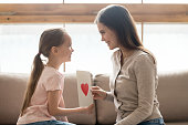 Profile cute daughter give loving mother postcard with red heart symbol show devotion care love sitting on couch in living room. Positive emotions mom presenting to child paper card occasion congrats