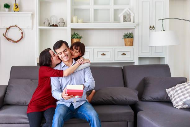 tochter und mutter überraschend vater mit geschenk zu hause im wohnzimmer, mutter mit kindern feiern vatertag - geschenke eltern weihnachten stock-fotos und bilder