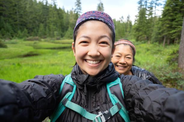 daughter and mother taking selfie while hiking along alpine lake - woman portrait forest foto e immagini stock