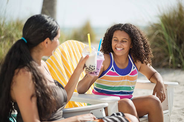 Daughter And Mother Toasting Boba Milk At Beach stock photo