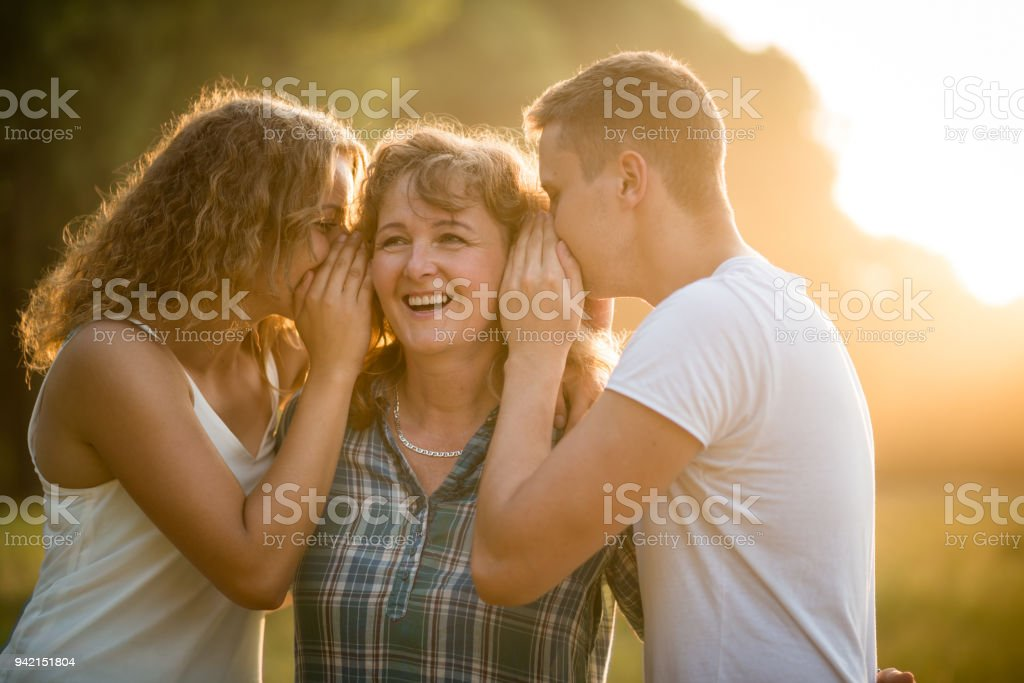 Tochter und Sohn Geheimnis in Mutters Ohr flüstern – Foto
