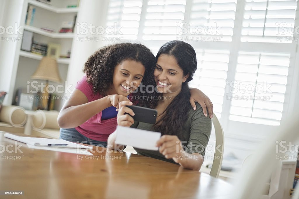 Daughter Assisting Mother To Deposit Check Through Smart Phone stock photo