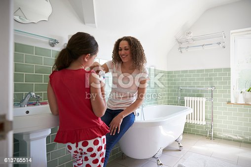 istock Daughter Brushing Teeth In Bathroom With Mother 613765514