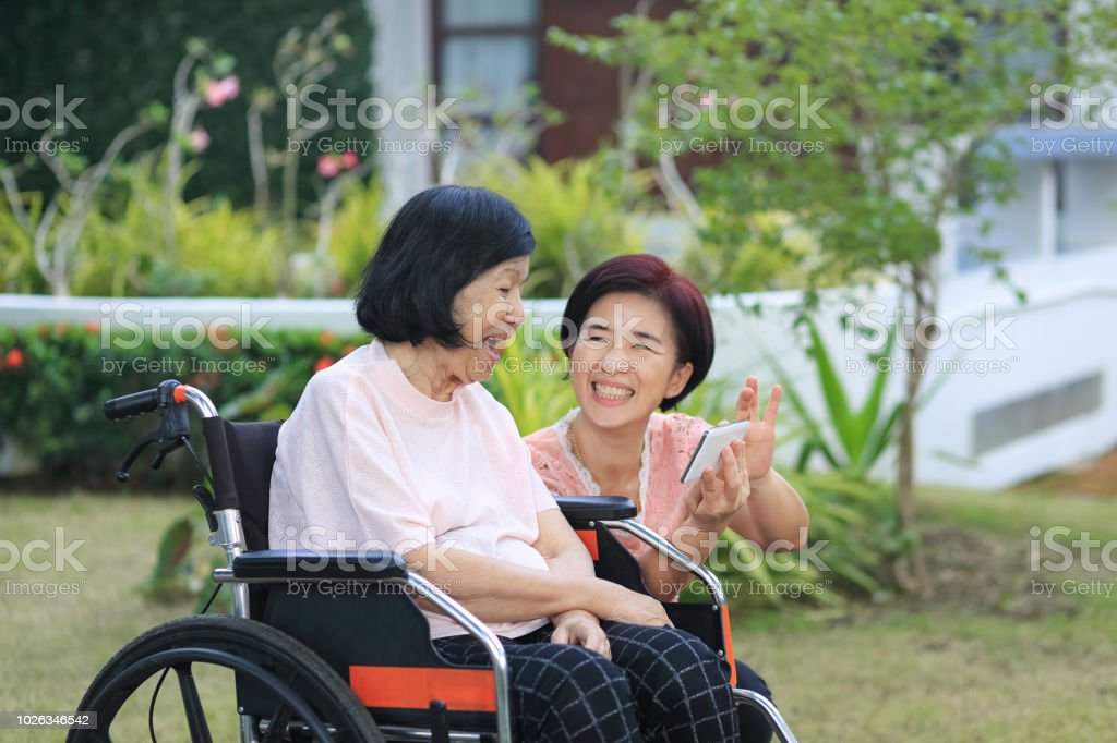 Daughter caring for the elderly asian woman ,do selfie, happy, smiles in backyard. stock photo