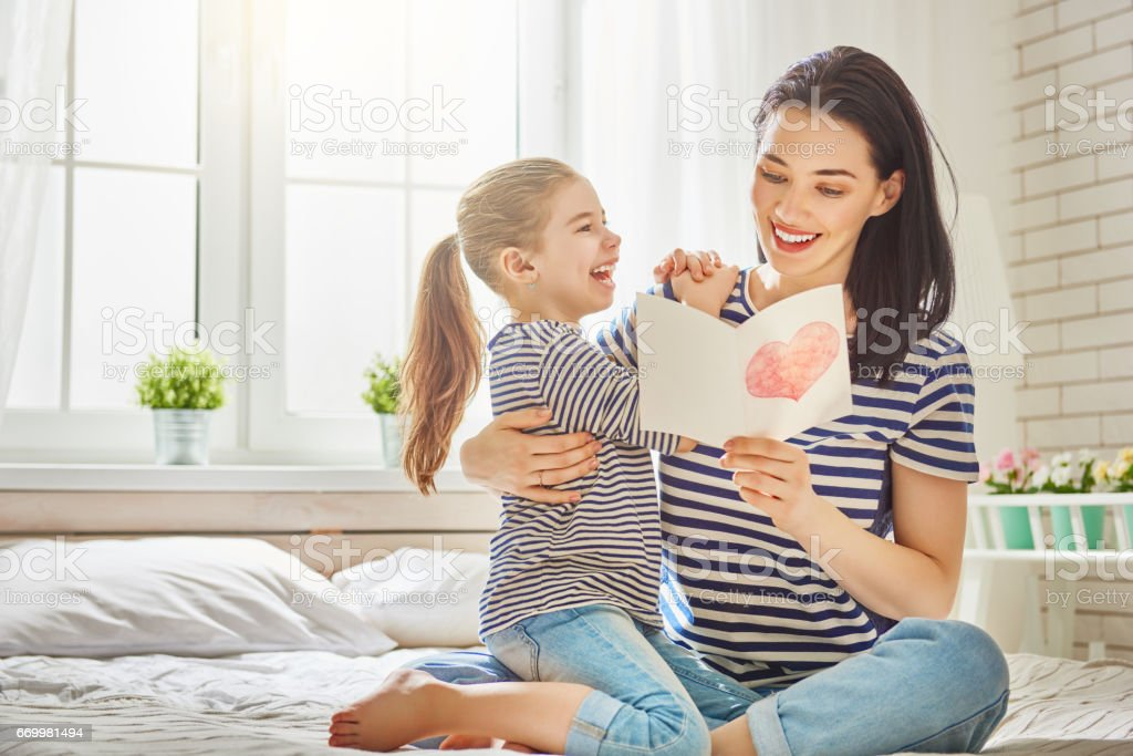 daughter congratulates mom stock photo