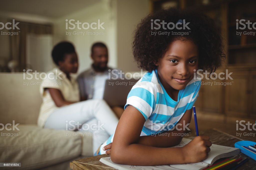 Daughter drawing on book while parents using laptop in background stock photo