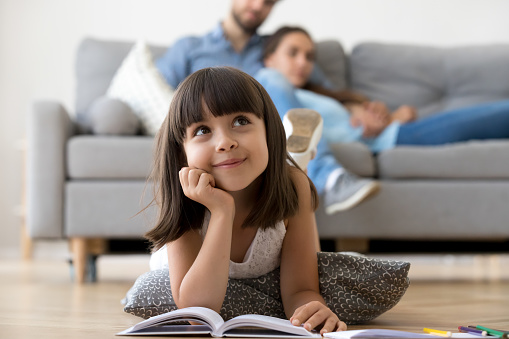 istock Daughter dreaming lying on warm floor with book at home 1070261892