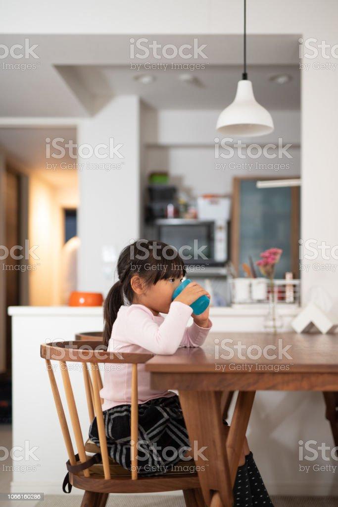 娘のミルクのコップ ストックフォト