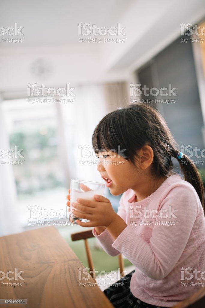 ミルクの入ったコップを飲む娘 ストックフォト