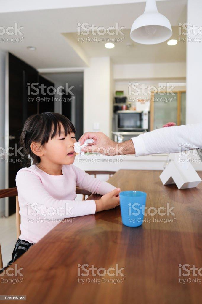 父とミルクのガラスを飲む娘 ストックフォト
