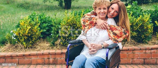 istock Daughter embracing her senior mother in wheelchair 959166714