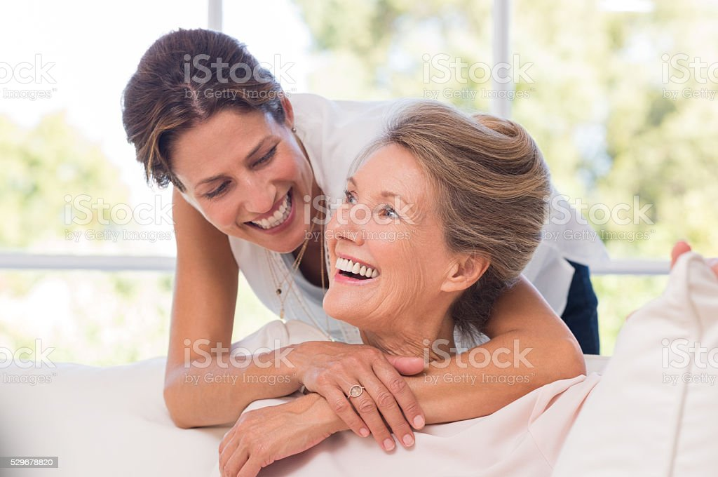Daughter embracing mother stock photo