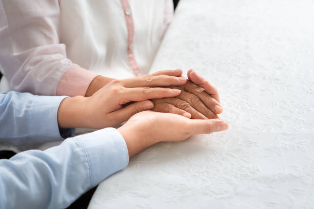 daughter encourage mom, young aged people holding old woman hand, mother day concept stock photo