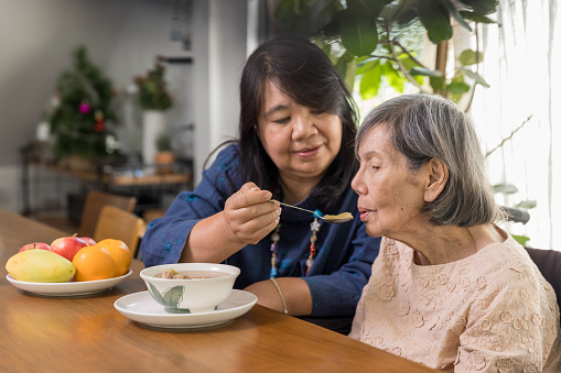Daughter feeding elderly mother with soup.Senior asian woman bored with food.