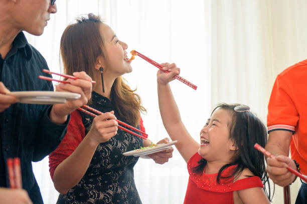 daughter feeding food to her mother in chinese new year reunion dinner - chinese new year stock pictures, royalty-free photos & images