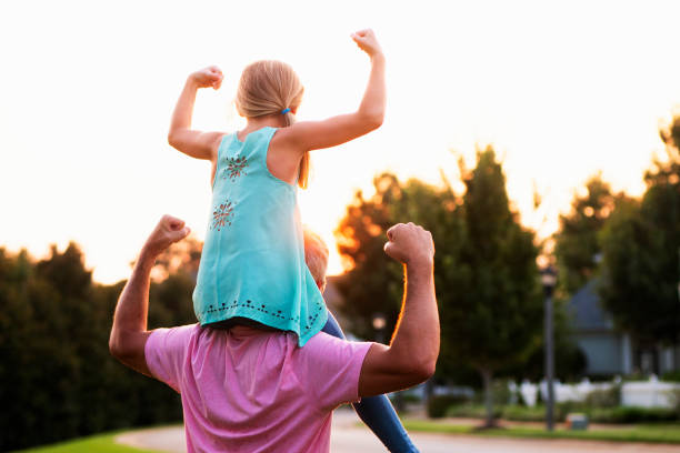 Daughter Flexing Muscles with Father Little girl on top of fathers shoulders holding arms up as in showing muscle. flexing muscles stock pictures, royalty-free photos & images